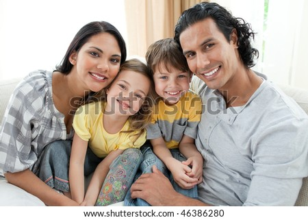 Portrait of a smiling family sitting on sofa at home