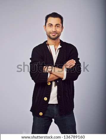 Portrait of a smiling fashionable guy standing in a studio - stock photo