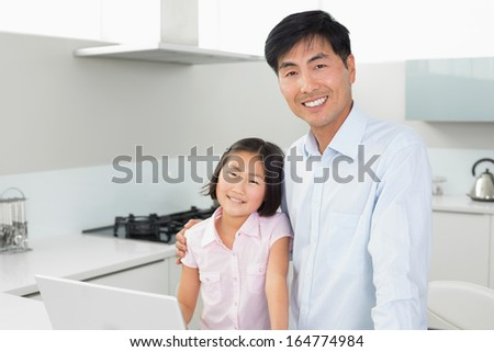 Portrait of a smiling father and young daughter with laptop in the kitchen at home