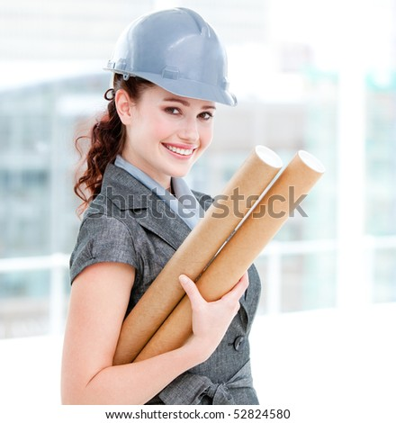 Portrait of a smiling female architect holding blueprints in the office