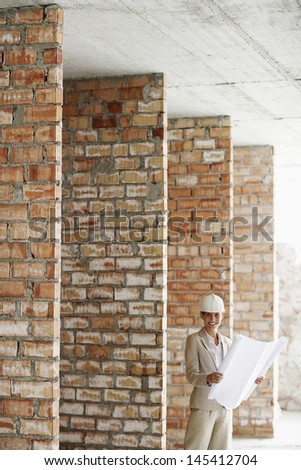 Portrait of a smiling female architect in hardhat with blueprints at construction site - stock photo
