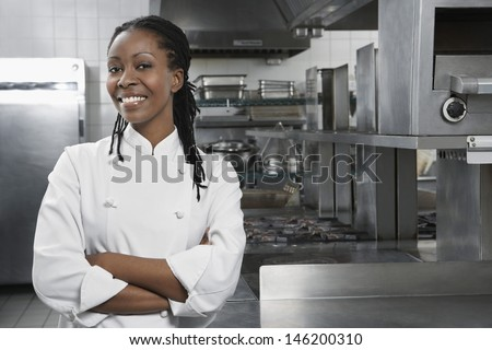 Portrait of a smiling female chef with hands crossed in the kitchen - stock photo