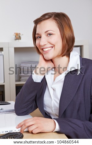 Portrait of a smiling female chief executive in the office at her desk - stock photo