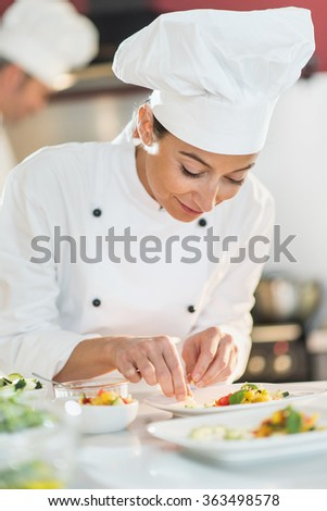 Portrait of a smiling female cook chef in her thirties. She is focus on preparing a colorful plate to serve. She is wearing white chef clothes and hat. Another man chef is cooking in the background. - stock photo
