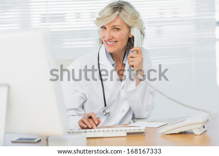 Portrait of a smiling female doctor with computer using phone at medical office