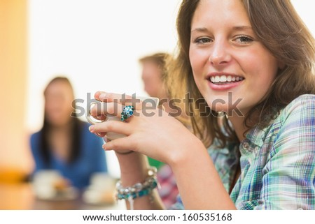 Portrait of a smiling female having coffee with students in background at  the coffee shop - stock photo