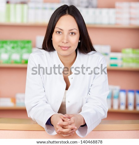 portrait of a smiling female pharmacist leaning on counter - stock photo