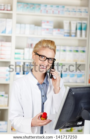 Portrait of a smiling female pharmacist on the phone at drugstore - stock photo