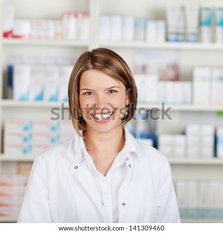 Portrait of a smiling female pharmacist with a beautiful big smile standing in her pharmacy - stock photo