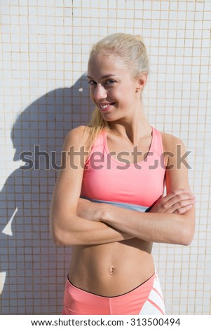 Portrait of a smiling female runner standing with crossed arms while taking break after morning run outdoors, happy fit woman with perfect figure enjoy rest after physical exercise in summer day - stock photo