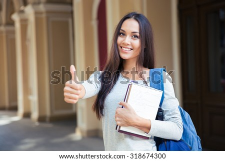 Portrait of a smiling female student showing thumb up outdoors - stock photo