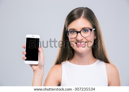 Portrait of a smiling female teenager in glasses showing blank smartphone screen isolated on a white background - stock photo
