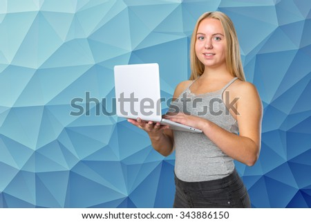 Portrait of a smiling female teenager standing with laptop - stock photo