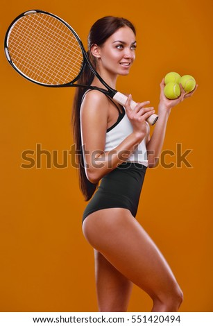 Portrait of a smiling female tennis player standing isolated on a orange background
