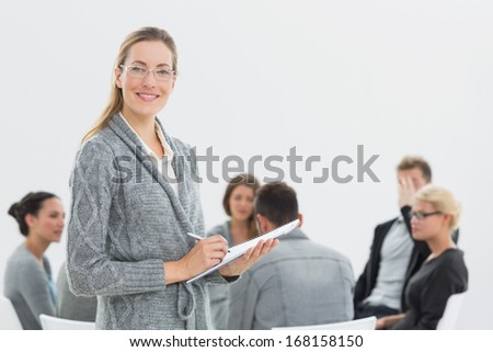 Portrait of a smiling female therapist with group therapy in session in background
