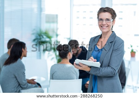 Portrait of a smiling female therapist with group therapy in session in background - stock photo