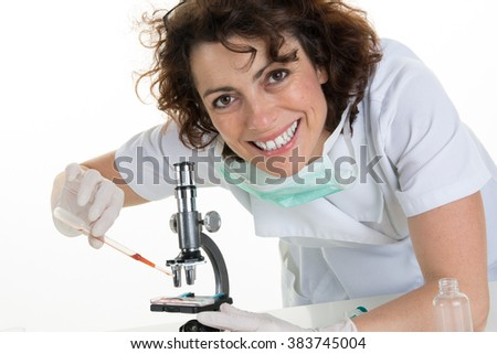 Portrait of a smiling female with researchers working on experiments in the laboratory - stock photo