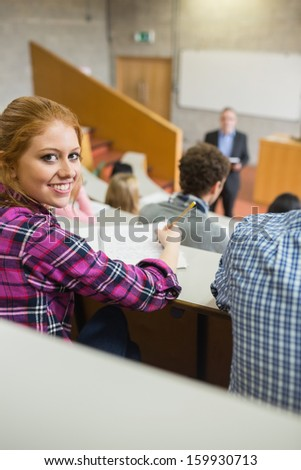 Portrait of a smiling female with students and teacher at the college lecture hall