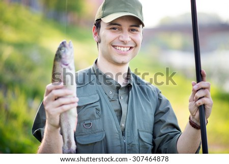 Portrait of a smiling fisherman holding a fish - stock photo