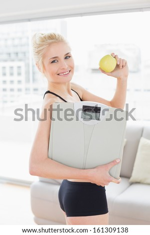 Portrait of a smiling fit young woman in sportswear holding scale and apple in fitness studio - stock photo