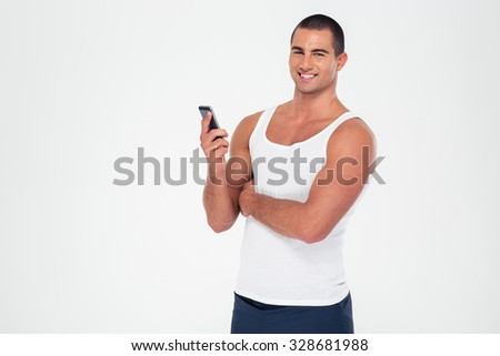 Portrait of a smiling fitness man holding smartphone and looking at camera isolated on a white background - stock photo