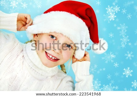 portrait of a smiling girl in a Santa hat and sweater. Christmas child - stock photo