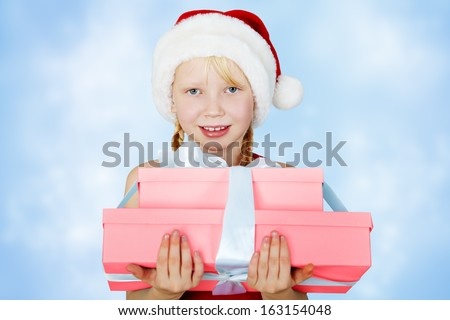 portrait of a smiling girl in a Santa hat with a gift in her hands - stock photo