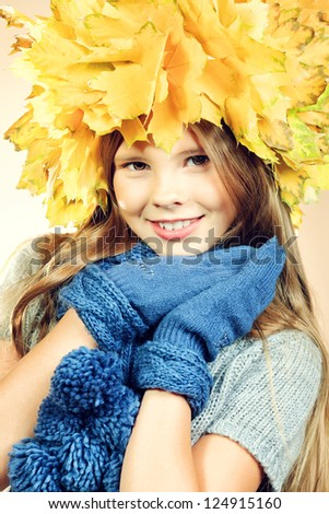 Portrait of a smiling girl in autumn clothes and a hat of maple leaves.