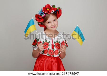 Portrait of a smiling girl in Ukrainian national headdress holding a Ukrainian flag on a gray background