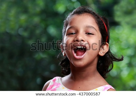 Portrait of a smiling girl of Indian origin in outdoor background