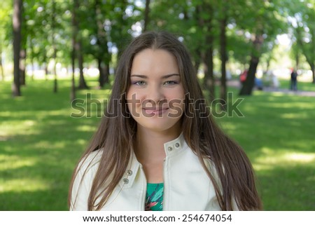 portrait of a smiling girl on green summer background