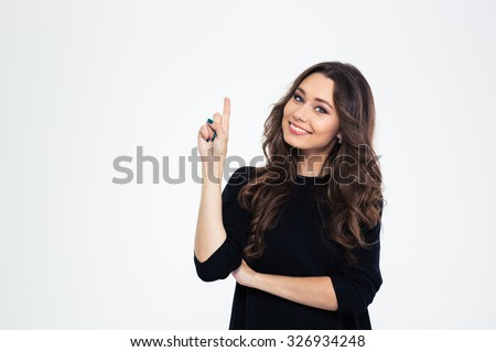 Portrait of a smiling girl pointing finger up at copyspace isolated on a white background - stock photo