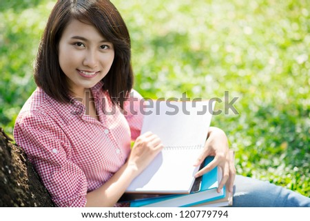 Portrait of a smiling girl studying outdoors
