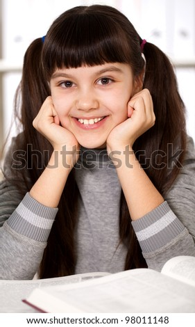 portrait of a smiling girl with a book - stock photo