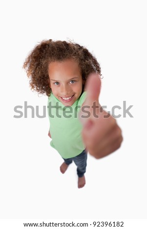 Portrait of a smiling girl with the thumb up against a white background