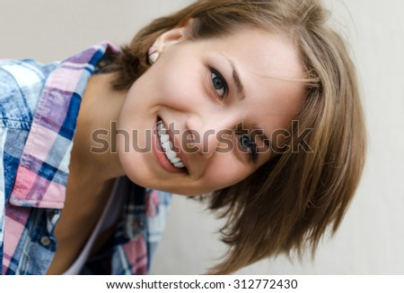 Portrait of a smiling girl with tilted head - stock photo