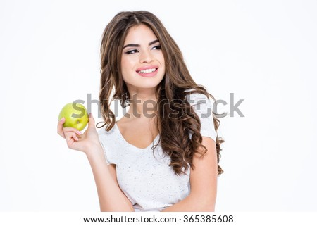 Portrait of a smiling gorgeous woman holding apple and looking away isolated on a white background - stock photo
