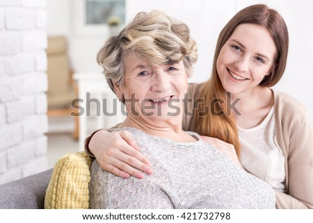 Portrait of a smiling granddaughter enfolding her grandmother