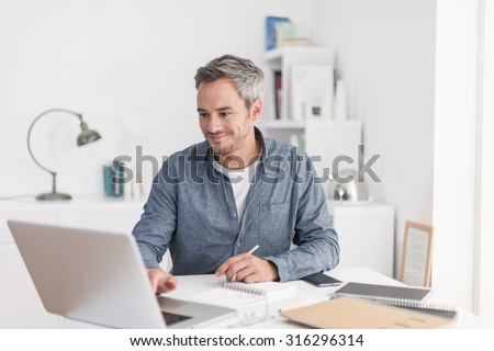 Portrait of a smiling grey hair man with beard, working at home on some project, he is sitting at a white table, drawing ideas on a white notebook, with his laptop in front of him. Focus on the man - stock photo