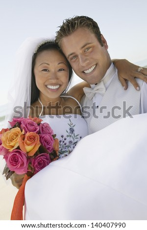 Portrait of a smiling groom carrying a happy bride outdoors - stock photo