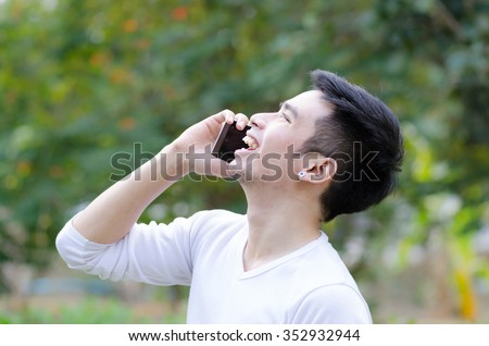 Portrait of a smiling guy talking on mobile phone outside, Asian man talking on mobile.