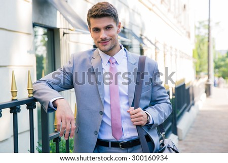 Portrait of a smiling handsome businessman standing outdoors and looking at camera - stock photo