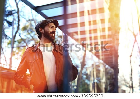 Portrait of a smiling handsome man holding hands in pocket while walking alone in urban setting, adult cheerful happy male dressed in trendy retro clothes standing on the street in a cool autumn day  - stock photo