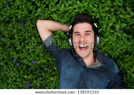 Portrait of a smiling handsome man with headphones outdoors - from above - stock photo