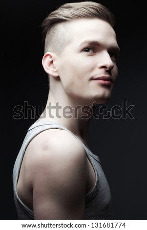 Portrait of a smiling handsome young man in casual gray sleeveless shirt posing over dark gray background. Perfect hair and skin. Urban hipster style.  Studio shot - stock photo