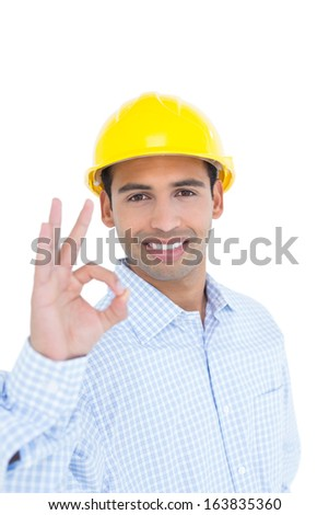 Portrait of a smiling handyman in yellow hard hat gesturing okay sign against white background