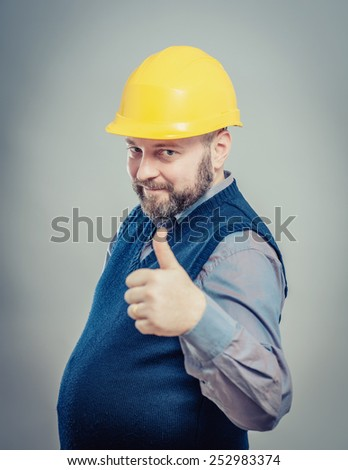 Portrait of a smiling handyman in yellow hard hat gesturing thumbs up  - stock photo