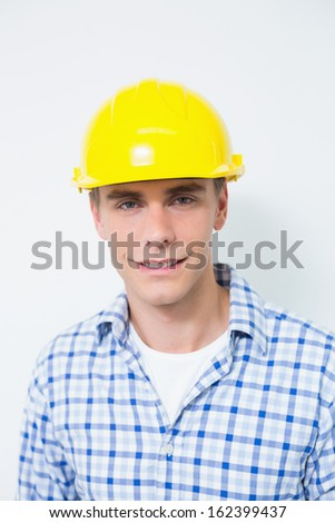 Portrait of a smiling handyman wearing a yellow hard hat against white background