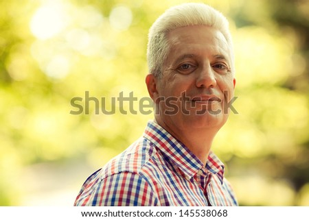 Portrait of a smiling happy mature (old) man in trendy casual shirt posing in the park. Sunny summer day. Copy-space. Close up. Outdoor shot - stock photo