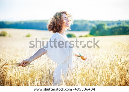 Portrait of a smiling happy woman in wheat field